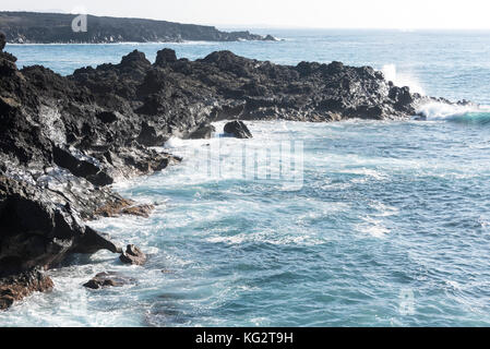 rocks with splashing waves near El Golfo in Lanzarote, Spain - Stock Photo