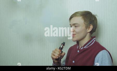Young man vaping an electronic cigarette. Vaper hipster smoke vaporizer. Young man enjoying a satisfying e-cigarette - Stock Photo