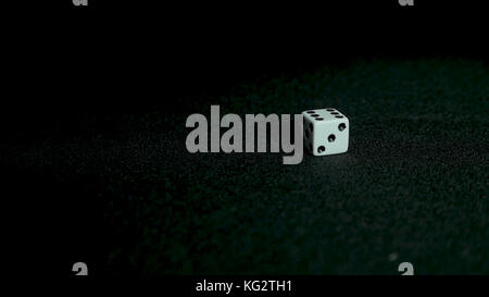 Female hand throwing dice on black background in slow motion. Two standard six-sided pipped dice with rounded corners - Stock Photo