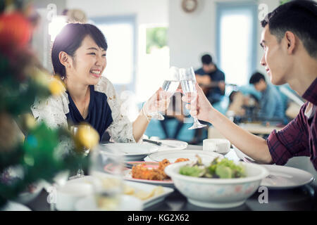 Asian young couple enjoying a romantic dinner  evening drinks while sitting at the dinning table on the kitchen - Stock Photo