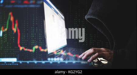 Internet crime and speculate stock concepts, Hacker working on computer laptop with downward stock graph background - Stock Photo