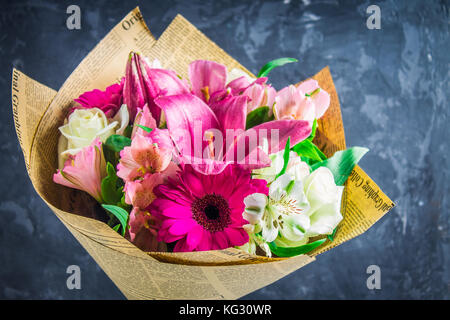 Bouquet of flowers from lily, gerbera, white roses and alstroemeria against the background of a dark concrete wall. - Stock Photo