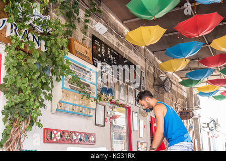 Unidentified man working at a cafe and restaurant at Alacati Town,a popular destination for traveling and vacation - Stock Photo