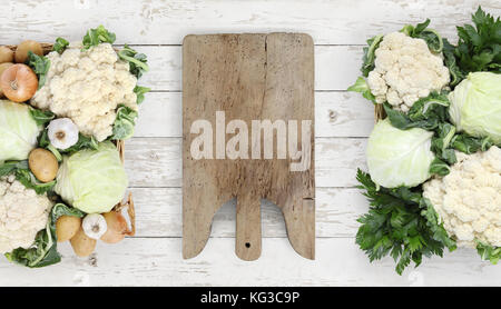 Healthy eating concept wooden cutting board with basket vegetables cabbage and cauliflower on kitchen white worktop, - Stock Photo