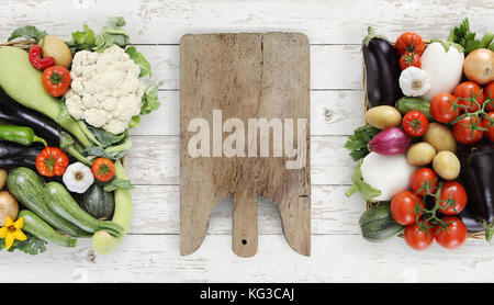 Healthy eating concept wooden cutting board with basket full of vegetables on kitchen white worktop, copy space, - Stock Photo