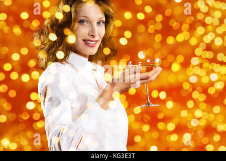christmas theme, smiling woman toast to the new year with glass of sparkling wine on blurred bright lights background - Stock Photo