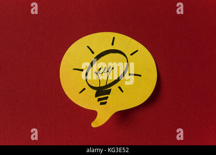 Yellow sticker with shape of speech bubble on red background - Stock Photo