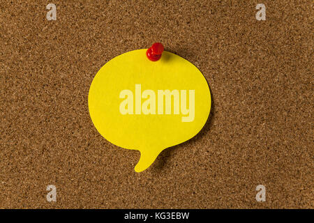 Yellow sticker with shape of speech bubble on cork board - Stock Photo