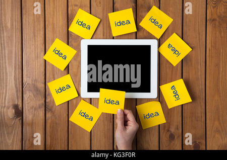 Businesswoman holding at word idea written sticky note and digital tablet. - Stock Photo