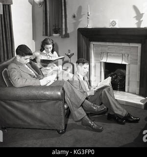 1950s, historical picture of three young adults in a front room, two sitting on a leather sofa, one sitting on the - Stock Photo