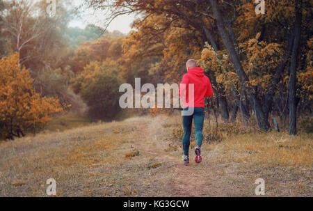 A slim athletic jogger in a black leggins and red jacket   runs on the colorful yellow autumnal forest hill. View - Stock Photo