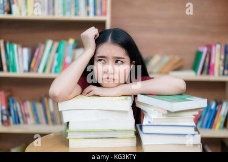 Asian woman student boring reading book at library with a lot of books in university. Asian student disheartened - Stock Photo