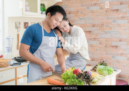 Young Asian couple preparing food together at counter in kitchen. Happy love couple concept. - Stock Photo