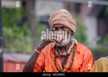 A sadhu baba is drinking tea on a clay pot at Varanasi ghat early in the morning. - Stock Photo
