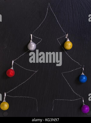 The New Year tree drawn with chalk. The drawing on a black board, brilliant Christmas tree decorations spheres are - Stock Photo