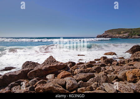 The seashore with large stones. Spain, Cantabria, coast of the Atlantic Ocean in the summer. Small waves run on - Stock Photo