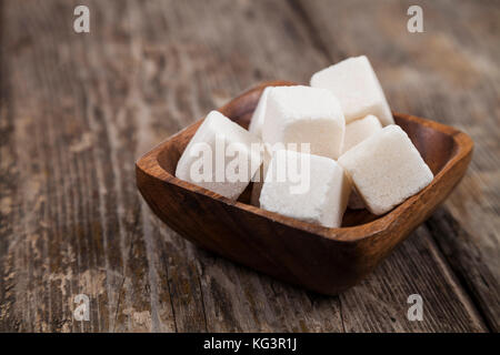 Sugar in a wooden bowl on an old wooden background - Stock Photo