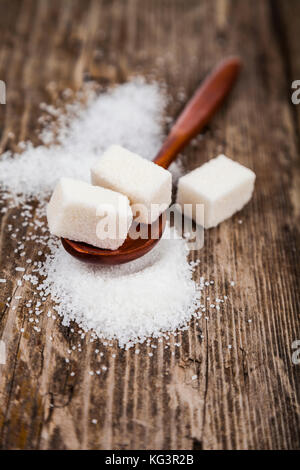 Wooden spoon with sugar on an old wooden background - Stock Photo