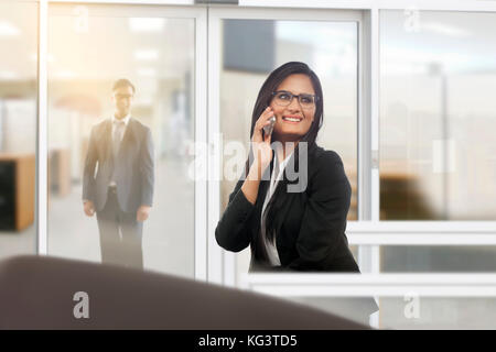 Businesswoman talking on mobile phone in office - Stock Photo