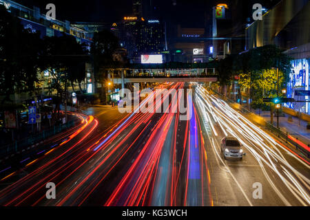 ast and intense traffic in the center of Bangkok at night. Traces from the headlights of cars. - Stock Photo