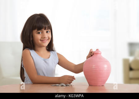 Portrait of little girl inserting coins in clay piggy bank - Stock Photo