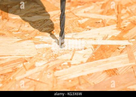 Wood drill bit. Drilling hole in board. - Stock Photo