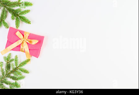 Christmas background. Christmas tree branch and present with gold ribbon on white background