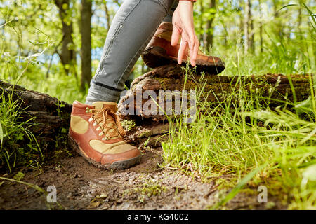 Leather hiking boots and hand of a female hiker in a low angle view as she steps over a fallen tree trunk in the - Stock Photo