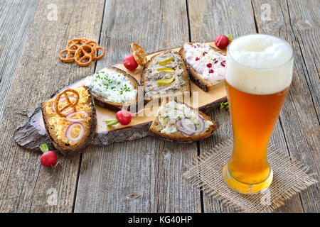 Hearty snack with different kinds of spreads on farmhouse bread served with a fresh yeast wheat beer on an old wooden - Stock Photo