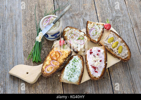 Hearty snack with different kinds of spreads on farmhouse bread served on an old wooden table - Stock Photo