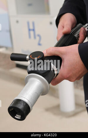 Man holding a hydrogen fuel filler nozzle for refueling hydrogen powered vehicles - Stock Photo