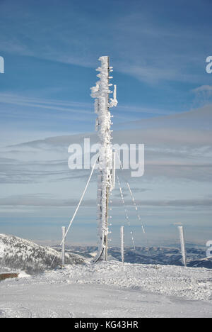 Telecommunication antenna on the top of the mountain, frozen and completely covered by snow and icicles against - Stock Photo