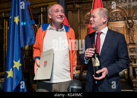 The cabaret artist, Emmanuel Peterfalvi (L), presents a bottle of red wine to Hamburg's first mayor Olaf Scholz from the Social Democratic Party of Germany (SPD) after the 42nd Naturalization ceremony in the Great Hall of the Hamburg town hall on 03 November 2017. The comedian from Paris known as Alfons was awarded the German citizenship on Friday. More than 100 natives of Hamburg celebrated their naturalization at the town hall ceremony. Photo: Christian Charisius/dpa