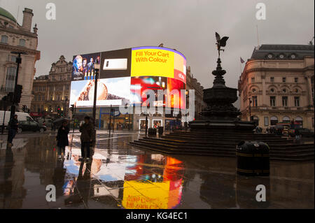 Piccadilly, London, UK. 4 November, 2017. New advertising signs the only bright splash of colour on a cold and wet - Stock Photo