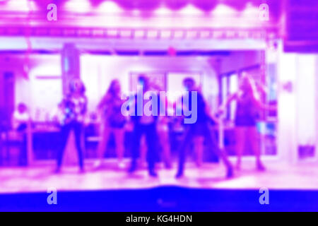 Blurred background of a group of people dancing in an indoor party - Stock Photo