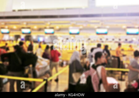 Blurred background of passengers falling in line in the check in area of the airport - Stock Photo