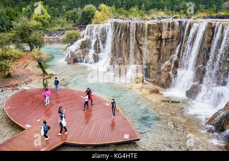 Lijiang, Yunnan, China - September 23, 2017: Tourists on the White Water River waterfall viewing platform in Blue - Stock Photo