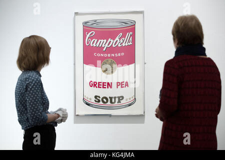 Emalee Beddoes-Davis museum curator and Helen Large look at Andy Warhol's, Campbell's green pea soup 1968, on display - Stock Photo