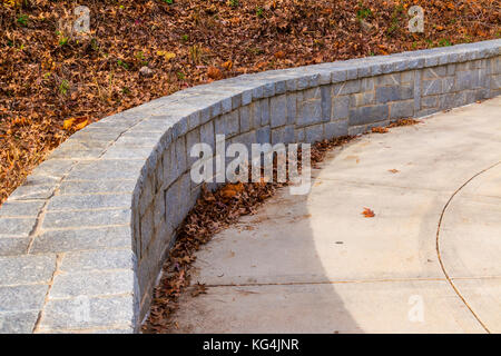 The tone fence on the side of concrete footpath and dry leaves in sunny autumn day - Stock Photo