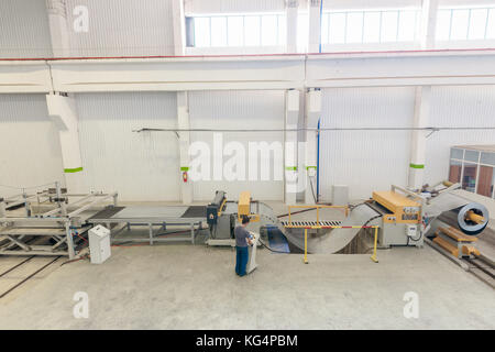 Machine for slitting of steel sheets in rolls. sheet metal working in rolls - Stock Photo
