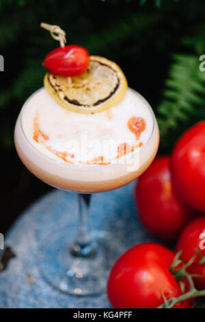 An alcoholic cocktail with egg foam garnished with a grape tomato and a slice of smoked lemon next to a cluster - Stock Photo