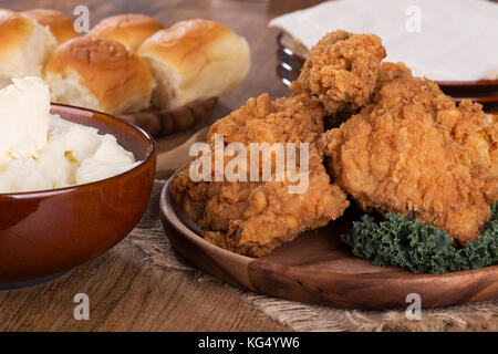 Fried chicken on a platter with mashed potatoes and rolls - Stock Photo
