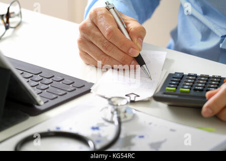 Healthcare costs and fees concept.Hand of smart doctor used a calculator for medical costs in modern hospital - Stock Photo