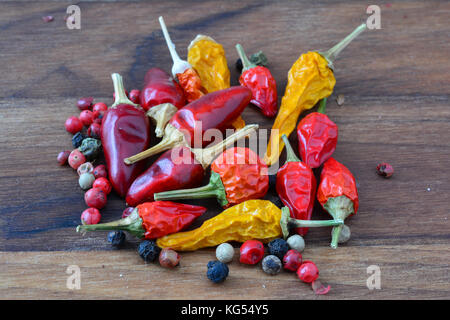 Hot spices, heap of mixed fresh and dry, red and yellow chilli peppers and red, black and white peppercorns on dark - Stock Photo