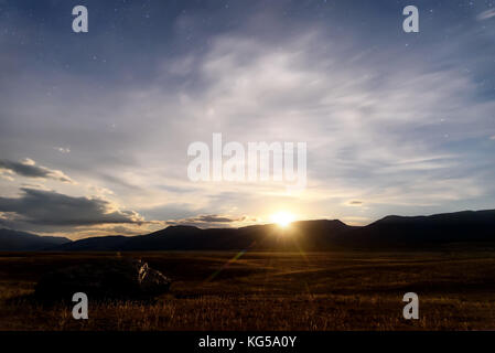Beautiful night landscape with a big stone in the steppe, moonrise, stars and clouds in the night sky against the - Stock Photo
