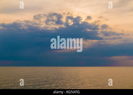 Soft view of the sun behind the rainy clouds over the calm sea - Stock Photo