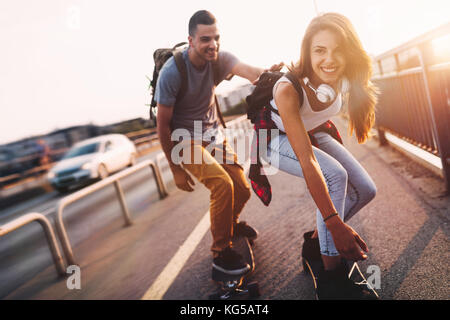 Young attractive couple riding skateboards and having fun - Stock Photo