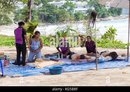 Tourists receiving massage on Surin Beach, Phuket, Thailand - Stock Photo