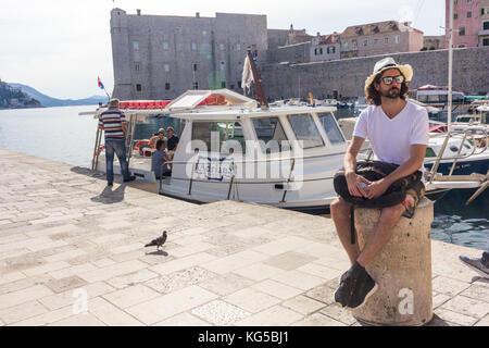 Man sat on post in Dubrovnik old town harbour, Croatia - Stock Photo