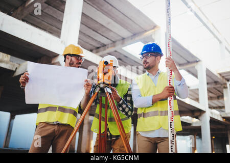 Portrait of construction engineers working on building site - Stock Photo